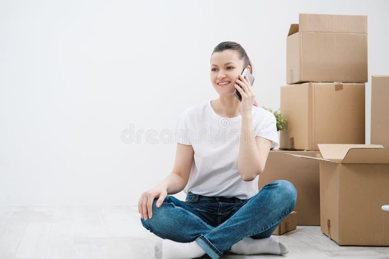 Het jonge mooie meisje met gekleurd haar in een witte T-shirt en jeans, die op de telefoon spreken en schrijft berichten tegen royalty-vrije stock afbeelding
