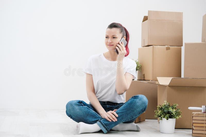 Het jonge mooie meisje met gekleurd haar in een witte T-shirt en jeans, die op de telefoon spreken en schrijft berichten tegen royalty-vrije stock afbeeldingen