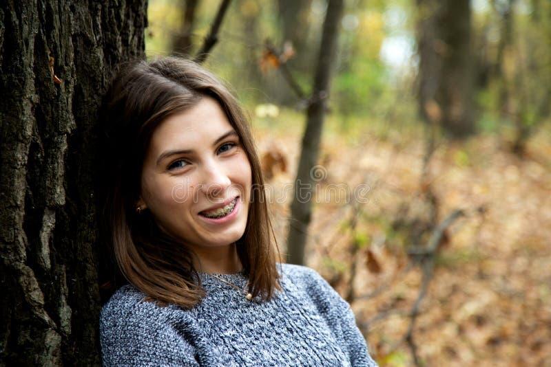 Het jonge mooie meisje met steunen op haar tanden in een grijze sweater zit in het de herfstbos dichtbij een grote boom en glimla royalty-vrije stock foto's