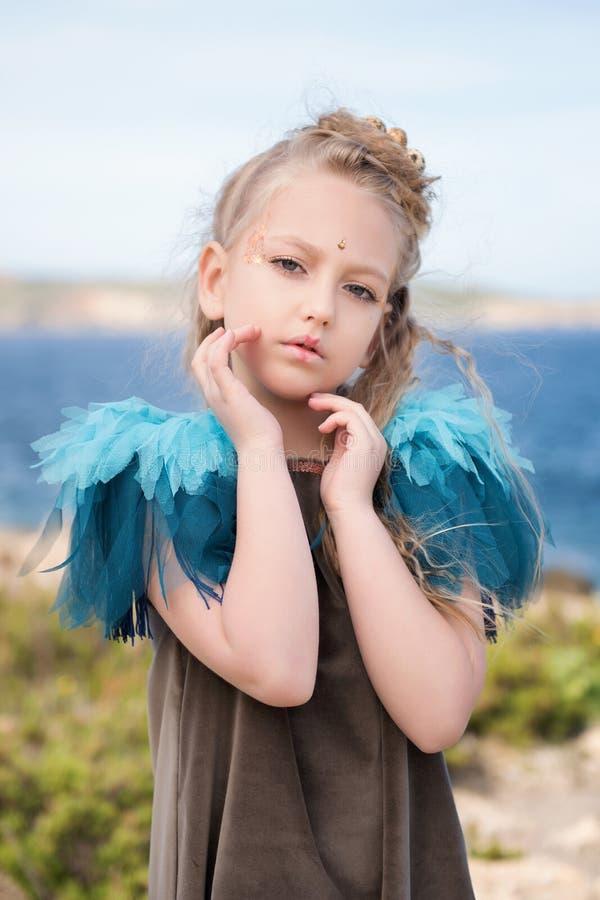 Het jonge mooie meisje model stellen op het strand met een vogeltjekostuum stock foto
