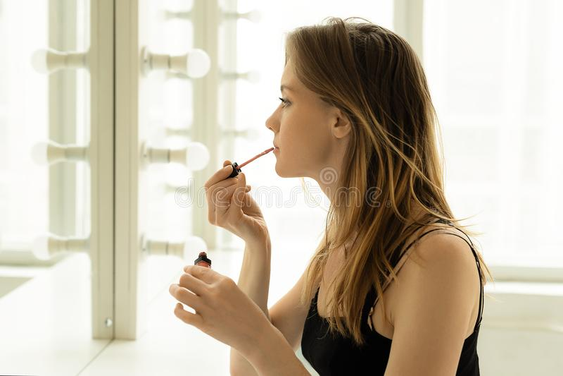 Het jonge mooie meisje schildert haar lippen dichtbij een spiegel royalty-vrije stock afbeeldingen