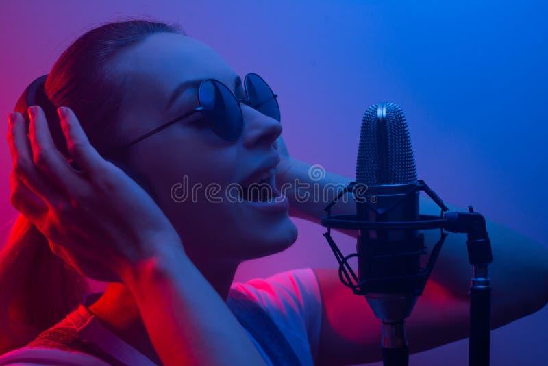Het jonge mooie meisje schrijft vocals, amusementsbedrijf, DJ, bijeenkomst, popmuziek In kleurenlicht, blauw-rood en rook stock afbeeldingen