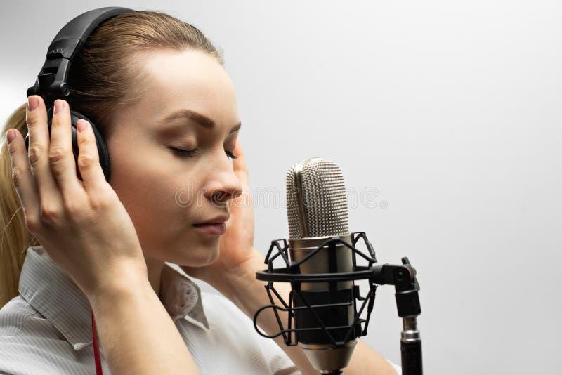 Het jonge mooie meisje schrijft vocals, radio, commentaarstemtv, leest poëzie, blog, podcast in studio op studiomicrofoon in hoof stock afbeelding