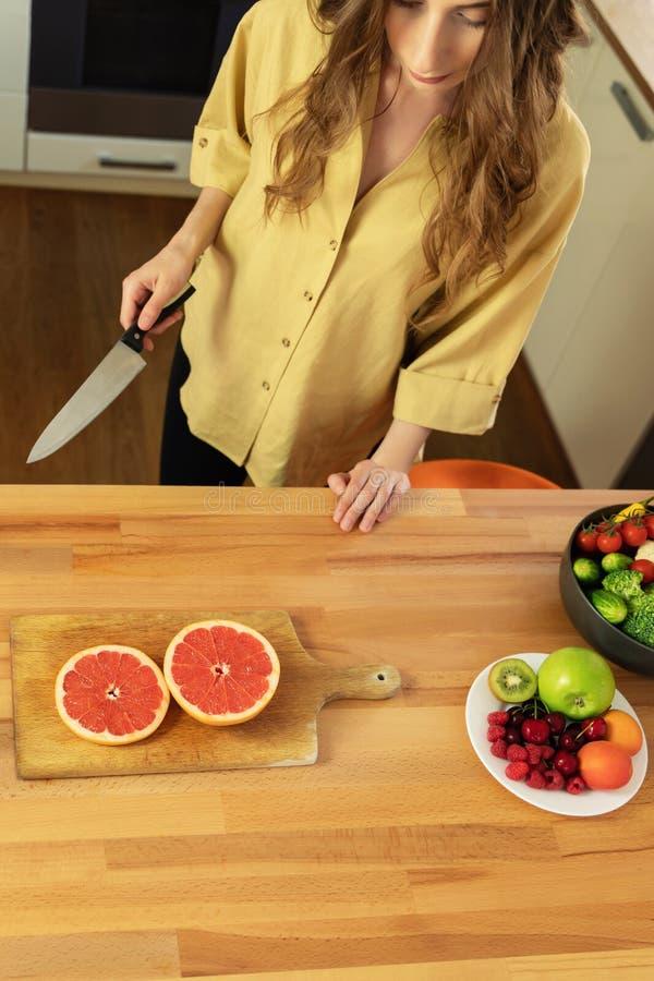 Het jonge mooie meisje snijdt een grapefruit royalty-vrije stock afbeeldingen