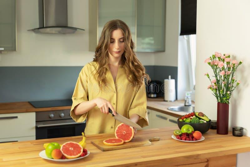 Het jonge mooie meisje snijdt een grapefruit stock fotografie