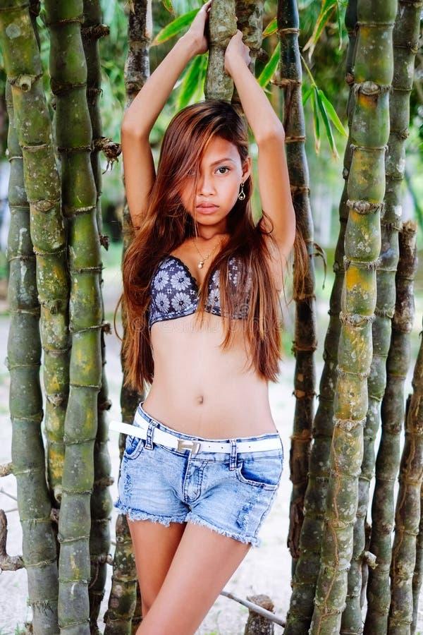 Het jonge mooie meisje stellen met de bamoobomen, het Hete concept van de de zomermanier stock afbeeldingen