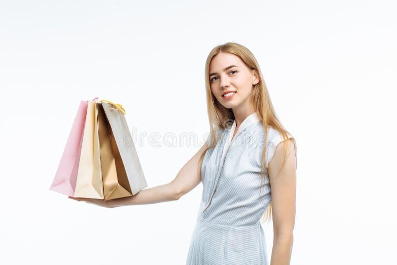 Het jonge mooie meisje stellen op witte achtergrond, met giftzakken, royalty-vrije stock foto