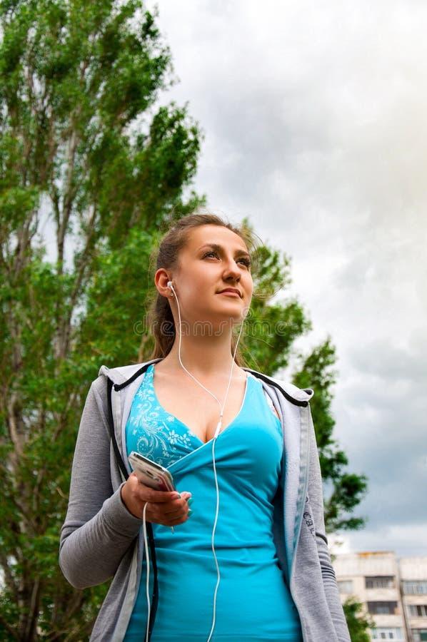 Het jonge Mooie Meisje stelt Straat in Ochtend in werking luistert Muziekhoofdtelefoons en geniet van dit Ogenblik Concepten gezo stock foto's