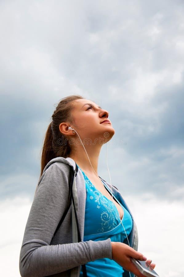 Het jonge Mooie Meisje stelt Straat in Ochtend in werking luistert Muziekhoofdtelefoons en geniet van dit Ogenblik Concepten gezo royalty-vrije stock foto