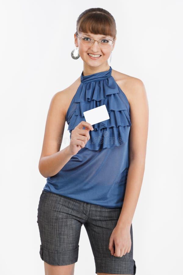 Het jonge mooie meisje toont een adreskaartje stock fotografie
