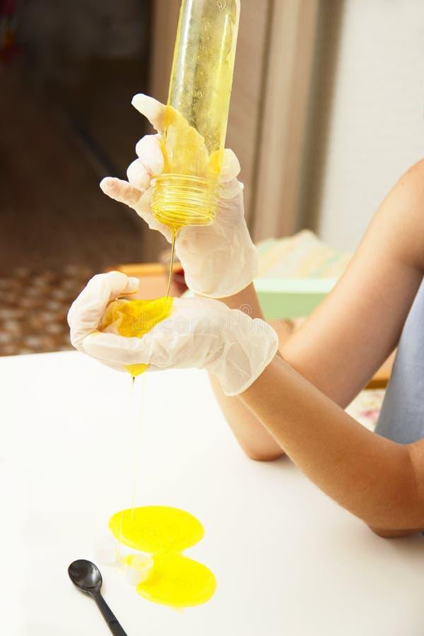 Het jonge mooie meisje toont hoe te om slijm te maken Het gele eigengemaakte slijm is een kinderen` s stuk speelgoed Tetraborate  stock foto's