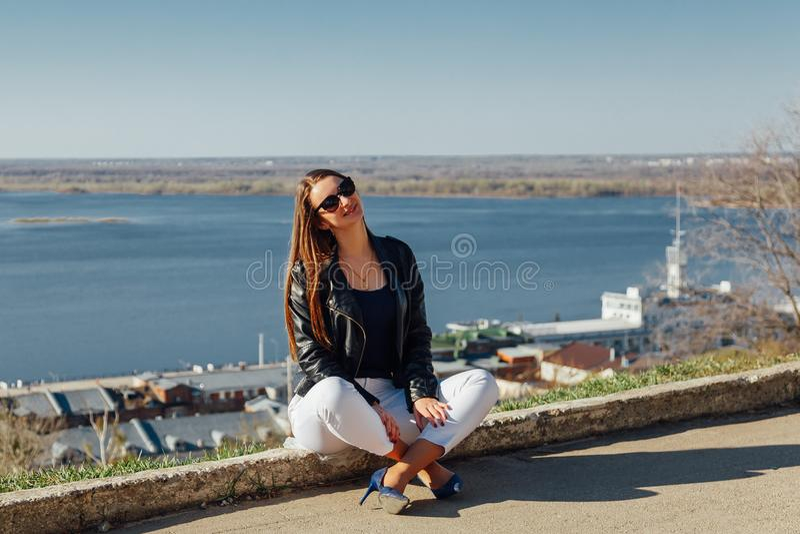 Het jonge mooie meisje zit op een baksteenverschansing stock foto's