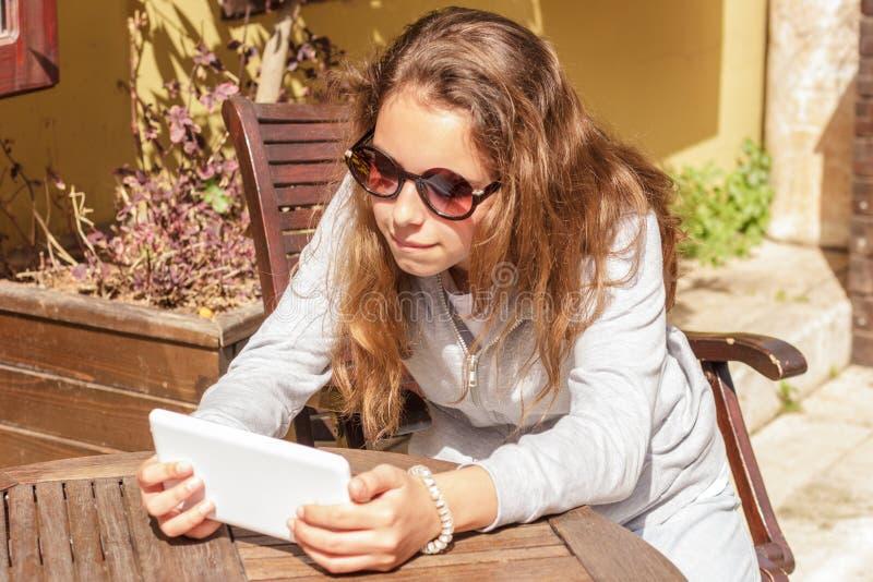 Het jonge mooie meisje in zonnebril let op een video op een tablet in een straatkoffie stock fotografie