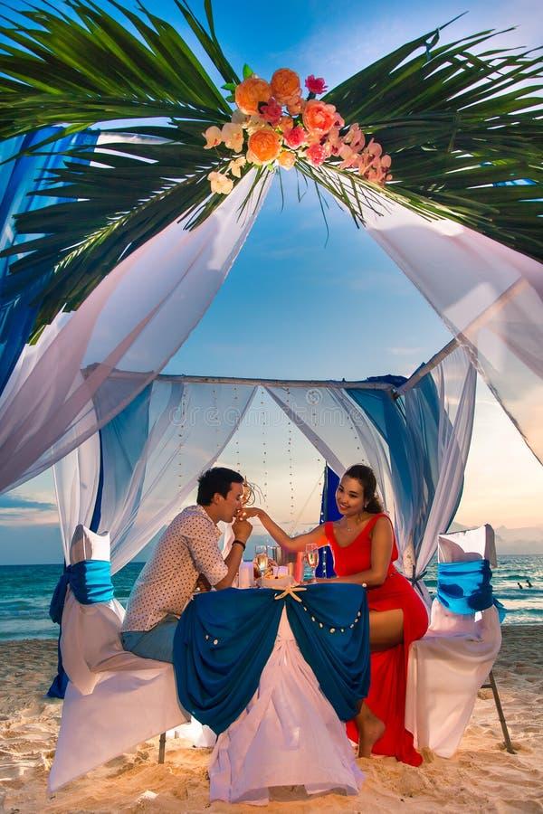 Het jonge mooie paar heeft een romantisch diner bij zonsondergang stock afbeeldingen