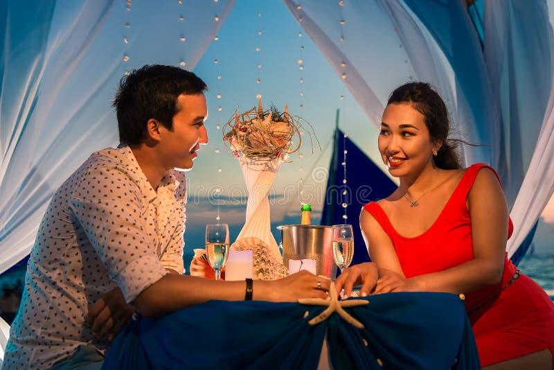 Het jonge mooie paar heeft een romantisch diner bij zonsondergang royalty-vrije stock foto's