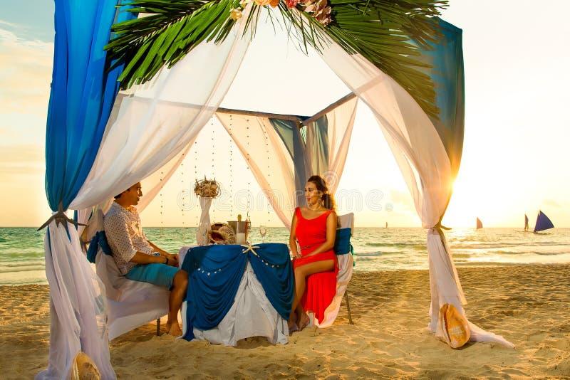 Het jonge mooie paar heeft een romantisch diner bij zonsondergang op een tro royalty-vrije stock afbeelding