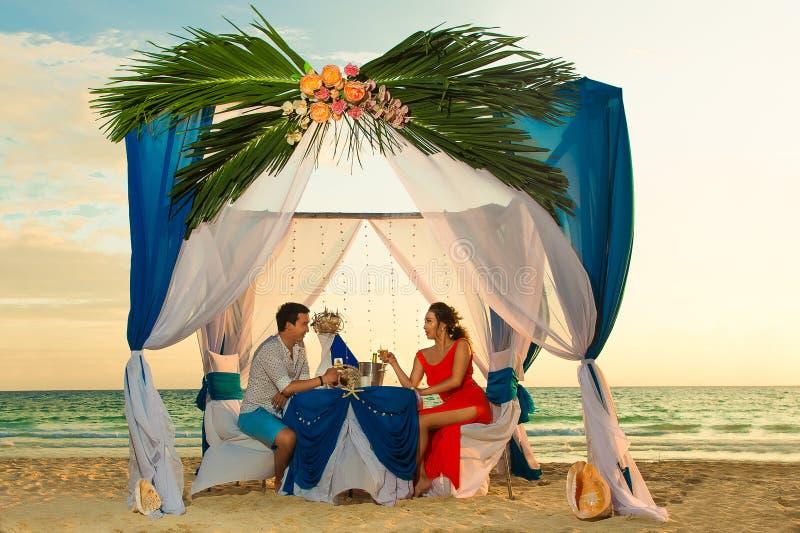 Het jonge mooie paar heeft een romantisch diner bij zonsondergang op een tro royalty-vrije stock foto's