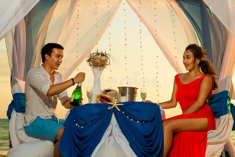 Het jonge mooie paar heeft een romantisch diner bij zonsondergang op een tro royalty-vrije stock afbeeldingen