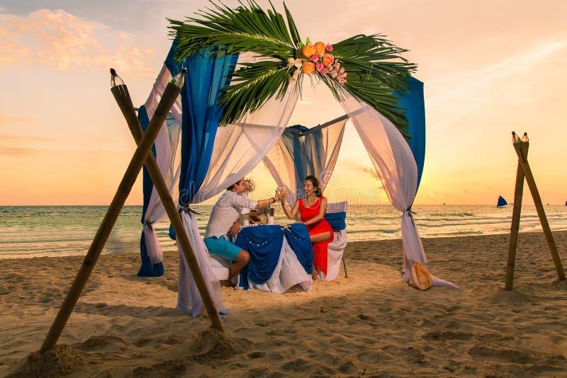 Het jonge mooie paar heeft een romantisch diner bij zonsondergang op een tro stock afbeelding