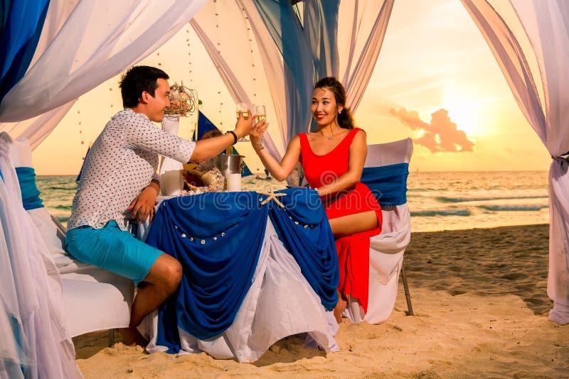 Het jonge mooie paar heeft een romantisch diner bij zonsondergang op een tro royalty-vrije stock foto