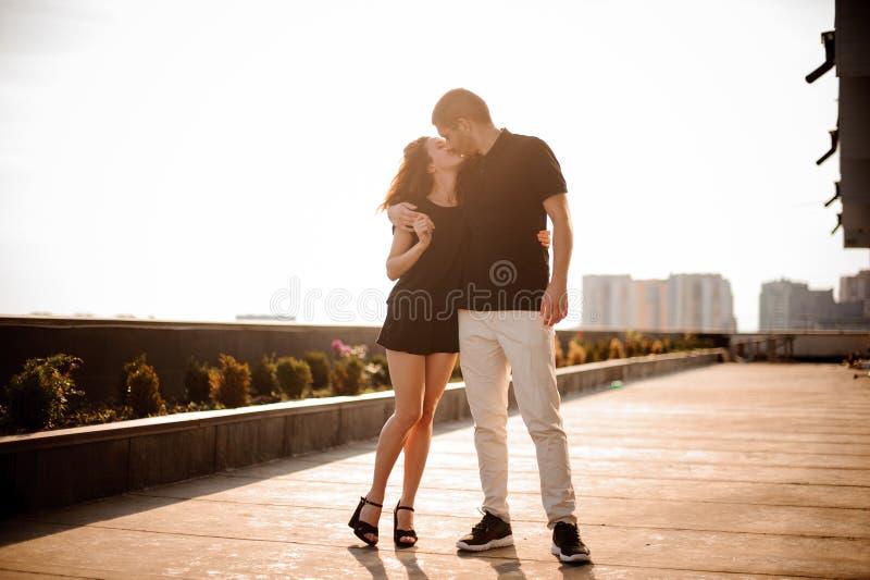 Het jonge mooie paar kussen bij zonsondergang royalty-vrije stock fotografie