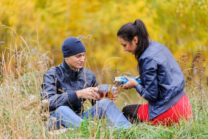 Het jonge mooie paar ontspant op de herfstaard stock fotografie