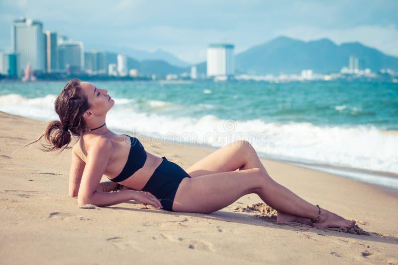 Het jonge mooie sexy donkerbruine bikini model leggen op overzees strand De exotisch reis van het land en rust concept royalty-vrije stock foto