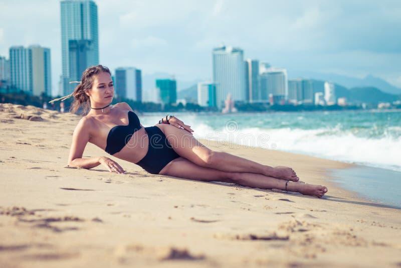 Het jonge mooie sexy donkerbruine bikini model leggen op overzees strand De exotisch reis van het land en rust concept stock foto