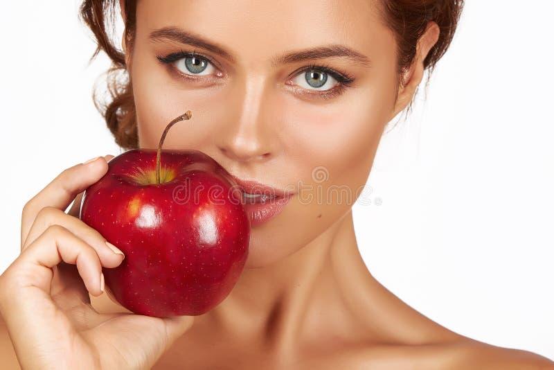 Het jonge mooie sexy meisje met donker krullend haar, naakte schouders en hals, die grote rode appel houden om van de smaak te ge stock afbeeldingen