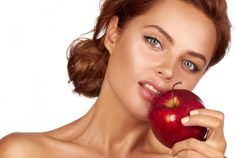 Het jonge mooie sexy meisje met donker krullend haar, naakte schouders en hals, die grote rode appel houden om van de smaak te ge stock fotografie