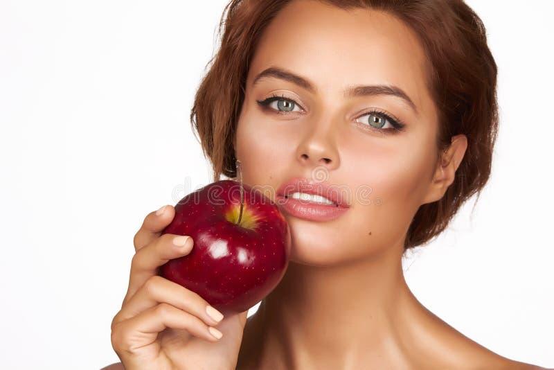 Het jonge mooie sexy meisje met donker krullend haar, naakte schouders en hals, die grote rode appel houden om van de smaak te ge stock foto's