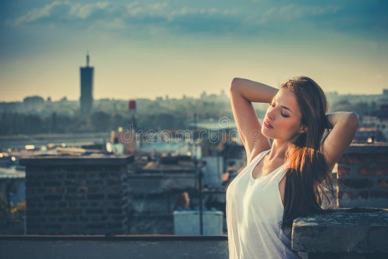 Het jonge mooie stadsmeisje geniet van in zonsondergang bij de dakzomer stock foto's