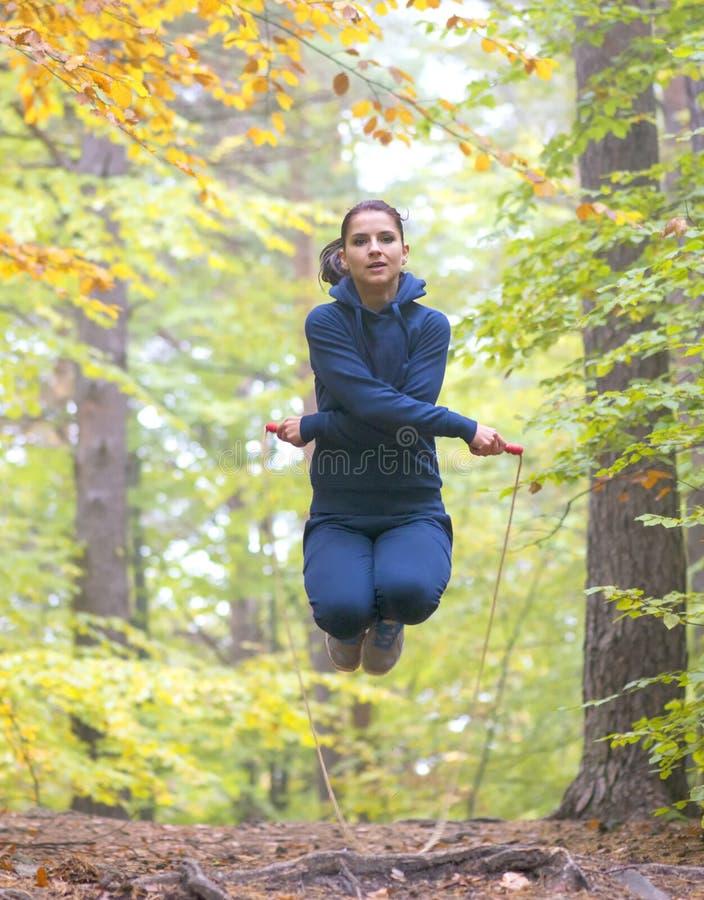Het jonge mooie touwtjespringen van de geschiktheidsvrouw in bos royalty-vrije stock foto