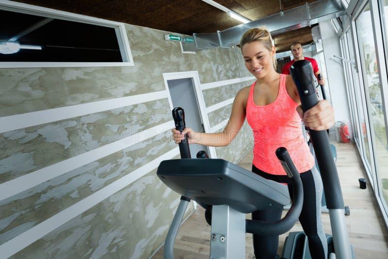 Het jonge mooie vrouw doen cardio in gymnastiek royalty-vrije stock foto's