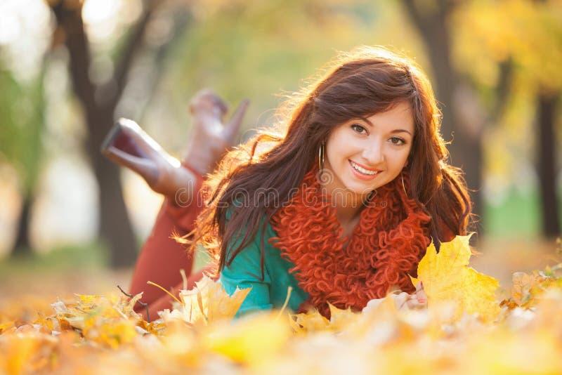 Het jonge mooie vrouw ontspannen in het de herfstpark royalty-vrije stock afbeeldingen