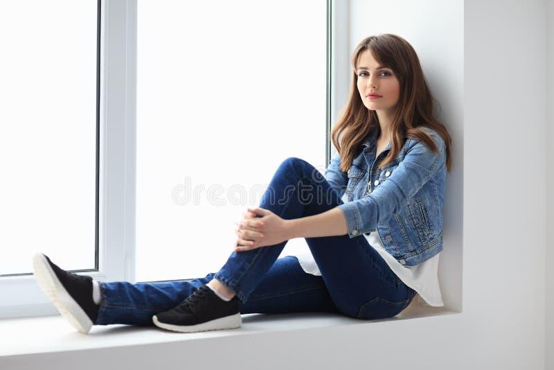 Het jonge mooie vrouw ontspannen op venstervensterbank royalty-vrije stock fotografie