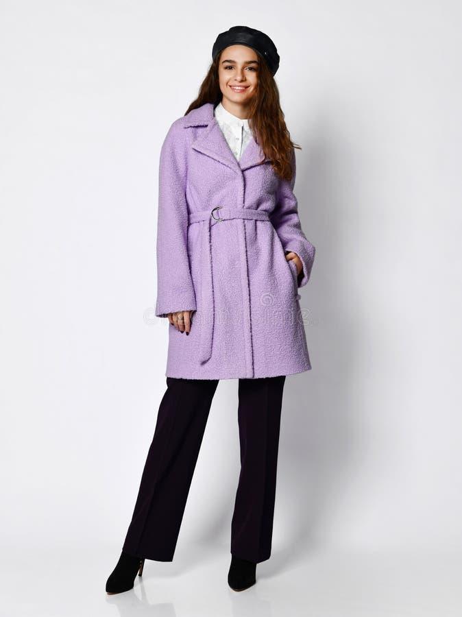 Het jonge mooie vrouw stellen in de nieuwe middelgrote laag van het de winterjasje van de lengtemanier toevallige roze, baret en  stock foto