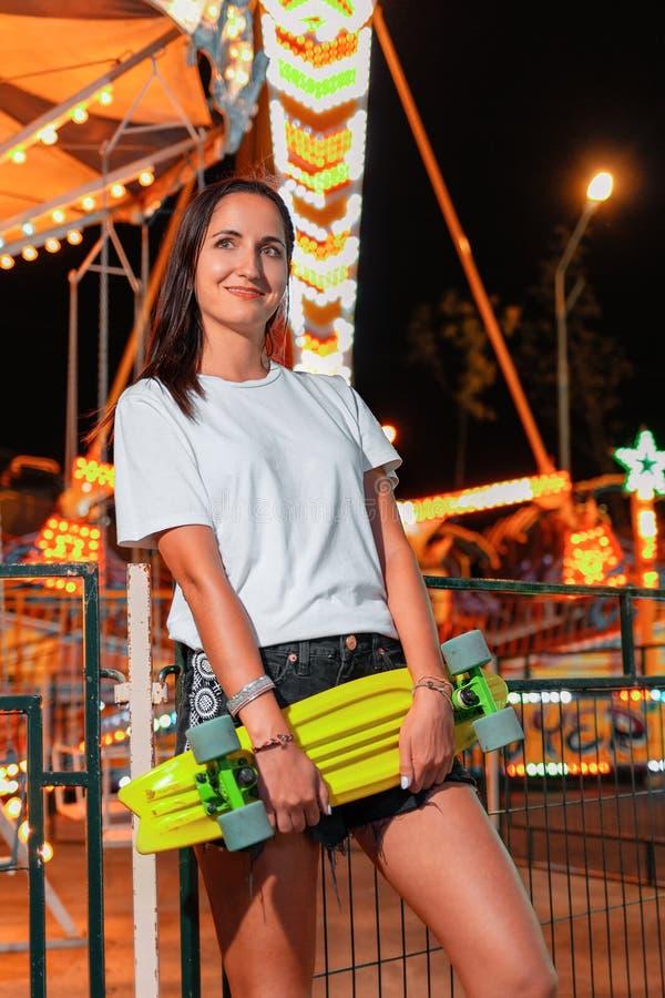 Het jonge mooie vrouw stellen met een skateboard in haar handen Op de achtergrond, een carrousel Het concept vakantie en royalty-vrije stock afbeeldingen