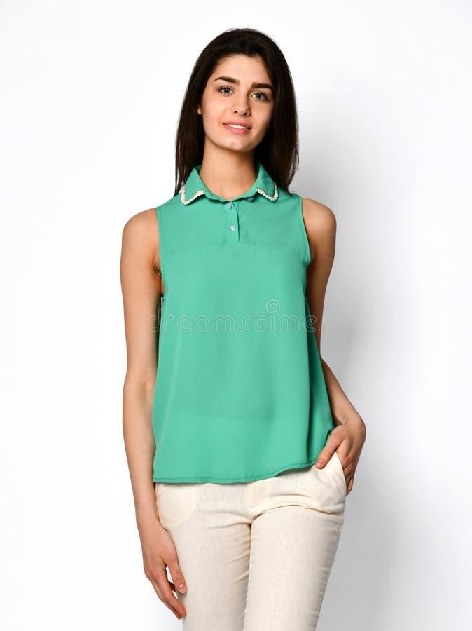 Het jonge mooie vrouw stellen in nieuw toevallig groen de blouseoverhemd van de bureaudoek op grijs royalty-vrije stock fotografie