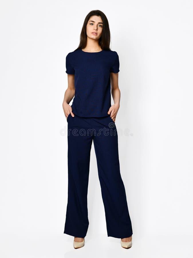 Het jonge mooie vrouw stellen in nieuwe donkerblauwe blouse met broek vormt toevallig kostuum royalty-vrije stock foto's