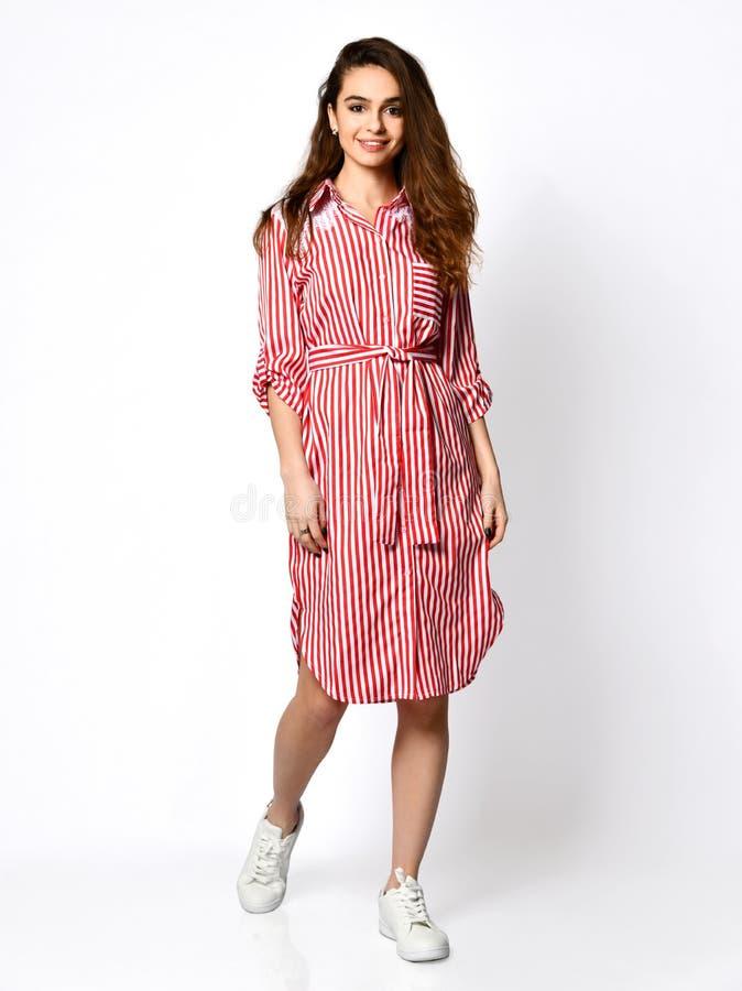 Het jonge mooie vrouw stellen in nieuwe lichtrose rode strepen vormt kleding op hoog heuvels volledig lichaam op een wit stock afbeeldingen