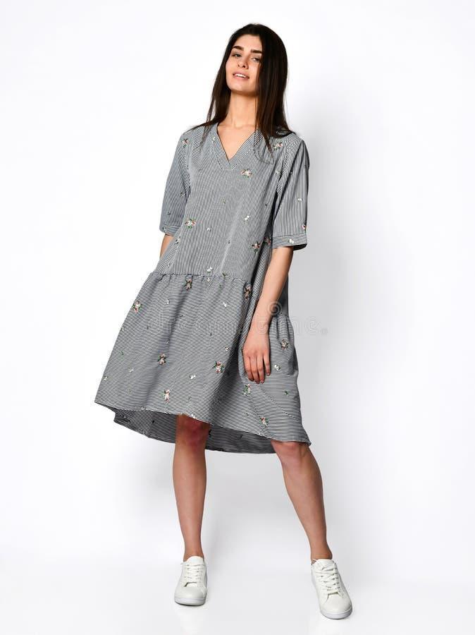 Het jonge mooie vrouw stellen in nieuwe ontwerp toevallige de zomer gestripte jeans kleedt volledig lichaam op grijs stock foto