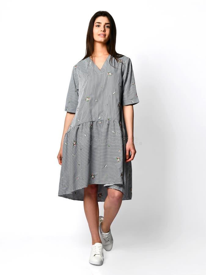 Het jonge mooie vrouw stellen in nieuwe ontwerp toevallige de zomer gestripte jeans kleedt volledig lichaam op grijs stock afbeelding