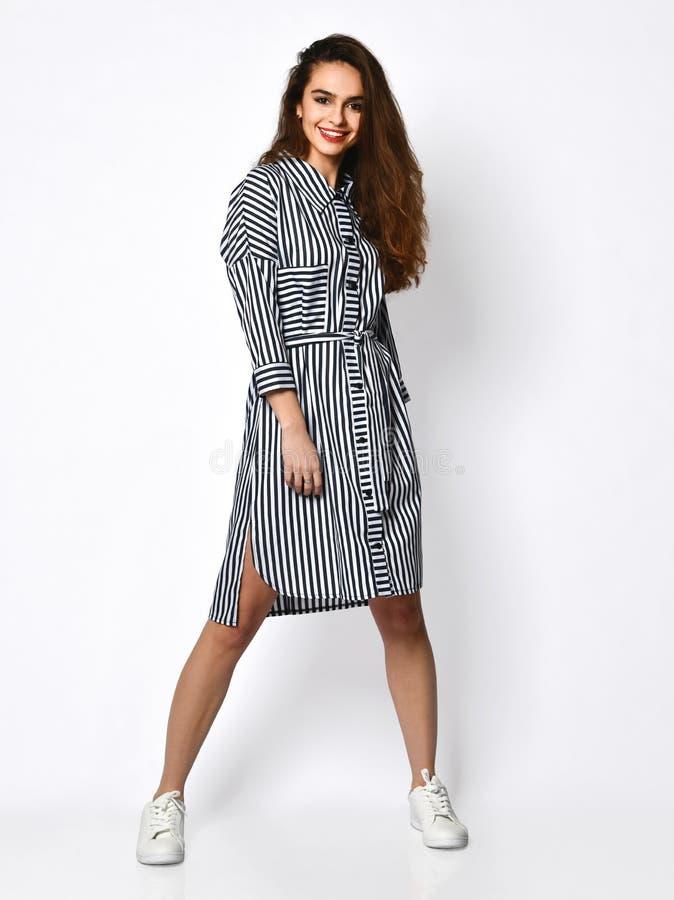 Het jonge mooie vrouw stellen in nieuwe ontwerp toevallige de zomer gestripte jeans kleedt volledig lichaam op grijs stock fotografie