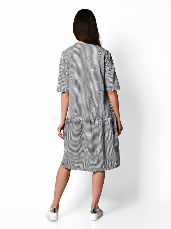 Het jonge mooie vrouw stellen in nieuwe ontwerp toevallige strepen springt kledings achtermening over grijs op stock afbeelding