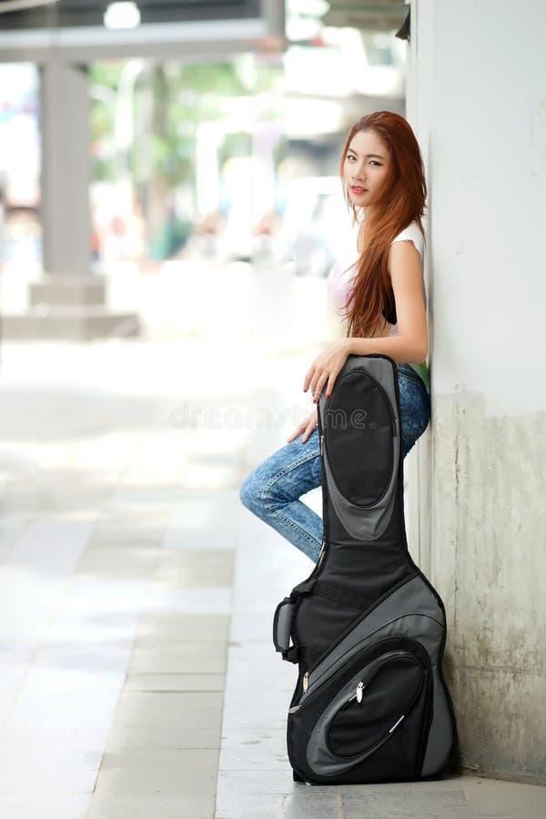 Het jonge mooie vrouw stellen openlucht met haar zak van de gitaarjol royalty-vrije stock afbeelding
