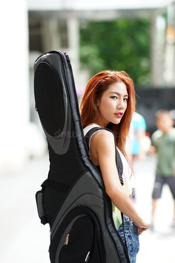 Het jonge mooie vrouw stellen openlucht met haar zak van de gitaarjol royalty-vrije stock foto's