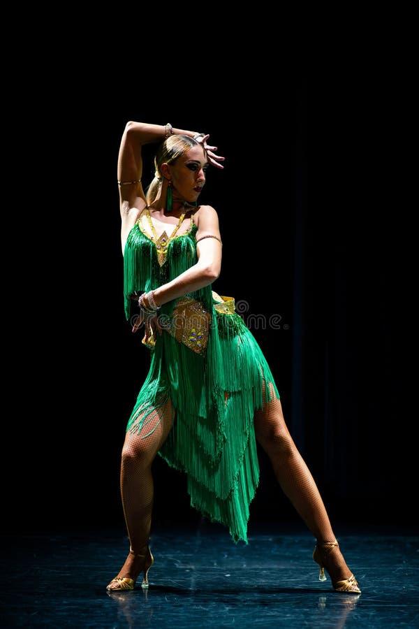 Het jonge mooie vrouwelijke danser stellen op zwarte achtergrond stock foto's