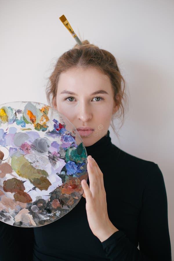 Het jonge mooie vrouwenkunstenaar stellen met borstels in studio royalty-vrije stock afbeelding