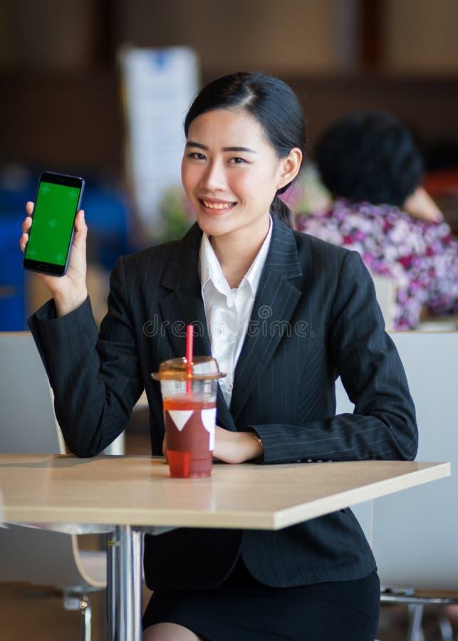 Het jonge mooie wijfje draagt online de zwarte pakwerken, winkelt via celtelefoon en laptop met een gelukkig en het glimlachen ge stock foto's